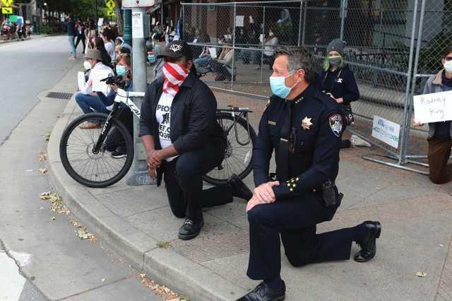В США полиция переходит на сторону митингующих и становится перед ними на колени